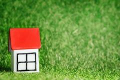 有红色屋顶的小屋在草背景 库存图片