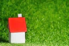 有红色屋顶的小屋在草背景 免版税库存图片