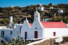 有红色屋顶的教堂在面对小山的米科诺斯岛 免版税库存照片