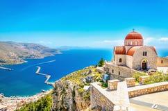 有红色屋顶的遥远的教会在峭壁,希腊 免版税库存照片