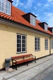 有红色屋顶的黄色房子 库存图片