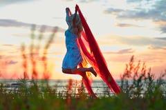 有红色布料的跳跃的女孩 库存照片