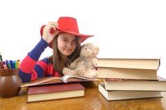 有红色帽子的女孩和她的玩具熊在桌上 免版税库存图片