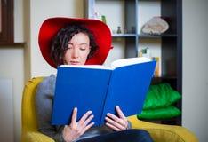 有红色帽子的少妇读书的 免版税库存图片