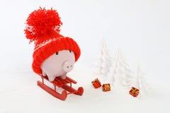 有红色帽子的贪心箱子有站立在雪的红色雪撬的大型机关炮的和是被雪包围住的树和三件礼物与gol -雪橇 库存图片