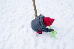 有红色帽子铁锹开掘雪的女孩 库存照片