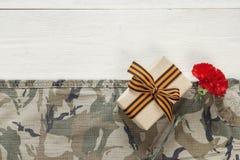 有红色康乃馨的礼物盒和在卡其色的b的圣乔治丝带 库存照片