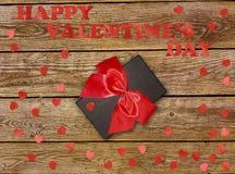 有红色弓丝带的礼物盒和在木桌上的纸心脏为情人节 库存照片