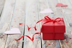 有红色弓丝带的礼物盒和在桌上的纸心脏为情人节 免版税库存照片