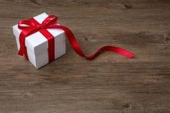 有红色弓的礼物盒在土气桌、圣诞节或者另一次庆祝上 免版税库存照片