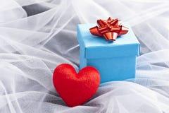 有红色弓的蓝色礼物盒在婚礼面纱 免版税库存图片