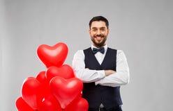 有红色心形的气球的愉快的人 免版税库存照片