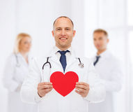 有红色心脏和听诊器的微笑的男性医生 库存照片
