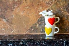 有红色心脏和黄色心脏的咖啡杯 库存图片