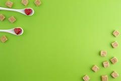 有红色心脏在他们和红糖立方体的两把白色匙子在绿叶背景 顶视图 复制文本的空间 免版税图库摄影