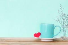 有红色心脏形状的咖啡杯杯子在木桌,拉丁文上 免版税库存图片