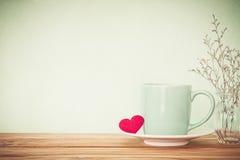 有红色心脏形状的咖啡杯杯子在木桌,拉丁文上 图库摄影