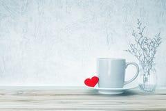 有红色心脏形状的咖啡杯杯子在木桌,拉丁文上 免版税库存照片