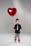有红色心脏气球的愉快的小男孩 库存图片
