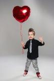 有红色心脏气球的愉快的小男孩 免版税库存图片