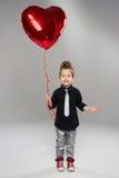 有红色心脏气球的愉快的小男孩 库存照片