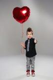 有红色心脏气球的愉快的小男孩 免版税图库摄影