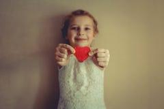 有红色心脏的一个女孩在她的手上 免版税库存照片