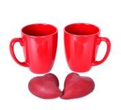 有红色心脏的两个红色杯子 免版税图库摄影