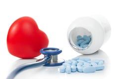 有红色心脏的听诊器和药片-在白色的演播室射击 免版税库存图片