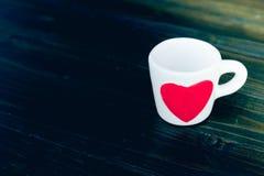 有红色心脏的咖啡杯在桌上 免版税图库摄影