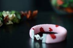 有红色心脏的图象的桃红色串珠的镯子在黑暗的背景的 免版税图库摄影