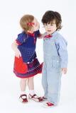有红色心脏的小美丽的女孩准备亲吻男孩 免版税图库摄影