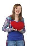 有红色心脏的微笑的美丽的十几岁的女孩在华伦泰的D 免版税库存图片