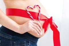 有红色心脏的怀孕的腹部 图库摄影