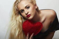 有红色心脏的性感的美丽的白肤金发的妇女。秀丽女孩。显示爱标志。华伦泰的Day.Passion 免版税图库摄影