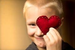 有红色心脏的愉快的孩子 库存图片