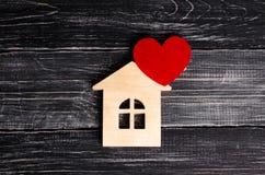 有红色心脏的木房子在黑木板背景  应用的一个通知象 恋爱地方,爱 库存照片