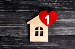 有红色心脏的木房子在黑木板背景  应用的一个通知象 恋爱地方,爱 免版税库存照片