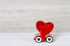有红色心脏的木玩具汽车 免版税库存图片