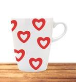 有红色心脏的白色杯子在白色隔绝的木桌上 免版税库存照片