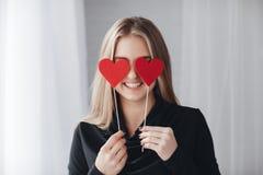 有红色心脏的美丽的妇女在爱天 免版税库存照片