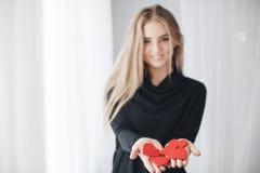 有红色心脏的美丽的妇女在爱天 库存照片
