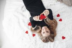 有红色心脏的美丽的妇女在爱天 库存图片