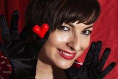 有红色心脏的美丽的年轻微笑的妇女在她的手上 库存图片