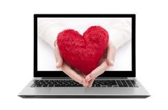 有红色心脏的膝上型计算机在妇女手上 库存照片