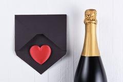 有红色心脏的香宾瓶在一个黑信封 免版税库存照片