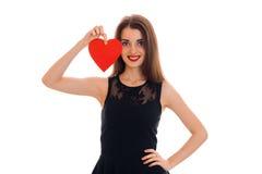 有红色心脏的年轻愉快的深色的夫人在手上微笑在照相机的隔绝在白色背景 背景蓝色框概念概念性日礼品重点查出珠宝信函生活纤管红色仍然被塑造的华伦泰 免版税库存照片