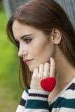有红色心脏项链的哀伤的体贴的妇女 免版税图库摄影