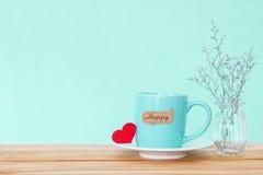 有红色心脏shapeand愉快的词标记的咖啡杯杯子在木 库存照片
