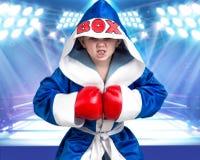 有红色手套的小男孩拳击手和长袍在圆环的背景中 冠军一点 大胜利 免版税库存照片